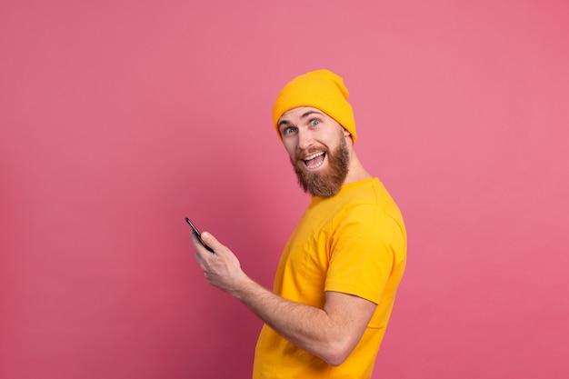 Europäischer schöner fröhlicher fröhlicher mann mit handy, das auf rosa lächelt