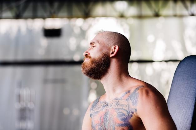 Europäischer tätowierter bärtiger, erschöpfter, starker, müder mann sieht nach dem training verschwitzt aus