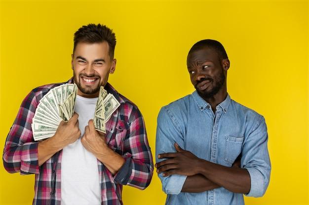 Europäischer typ mit viel geld in beiden händen lächelt glücklich und afroamerikanischer typ hat nichts, was ihn in informeller kleidung anguckt