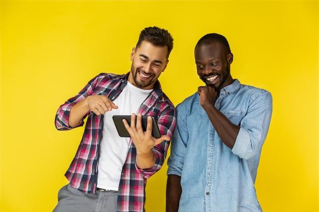 Europäischer typ zeigt etw auf dem tablet und er lacht zusammen mit afroamerikaner