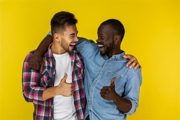 Europäischer und afrikanischer mann, der daumen miteinander lächelt und zeigt