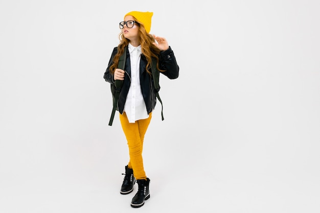 Europäisches attraktives mädchen gekleidet in einen gelben hut, eine brille und eine lederjacke mit einem rucksack auf dem rücken in voller wachstum auf weißer wand mit copyspace