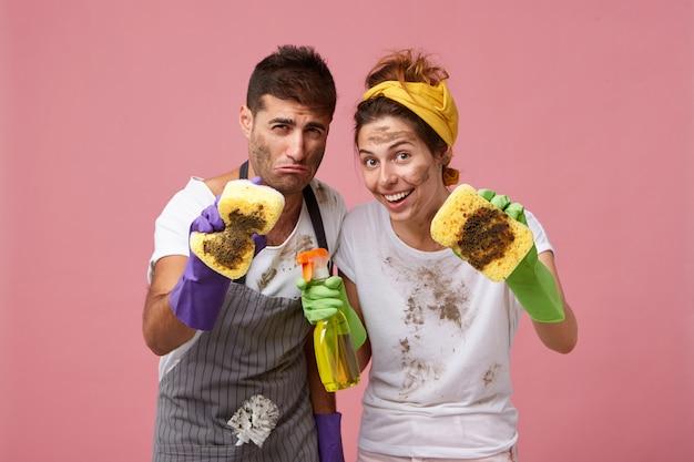 Europäisches ehepaar wischt den staub mit schwämmen und reinigungsmittel ab