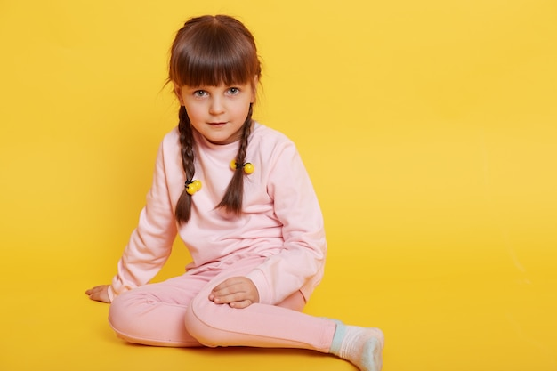 Europäisches entzückendes mädchen, das auf boden sitzt und blassrosa hosen und pullover trägt, lokalisiert über gelbem hintergrund, schaut auf kamera, dunkelhaariges weibliches kind mit zöpfen.