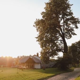 Europäisches holzhaus in einer malerischen landschaft bei sonnenuntergang im sommer