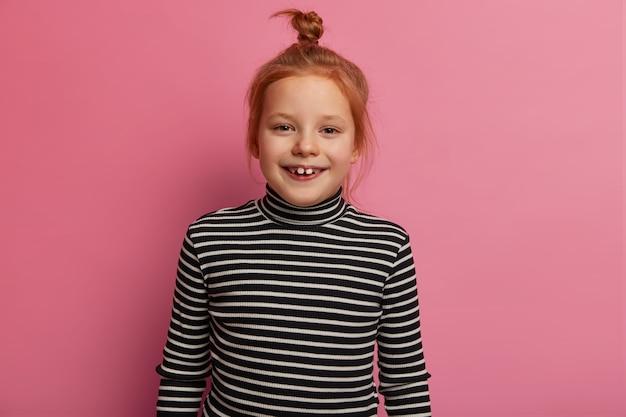 Europäisches kleines mädchen steht lässig über rosa pastellwand, hat ingwerhaarbrötchen, trägt schwarz-weiß gestreiften rollkragenpullover, ist gehorsames kind, schaut amüsiert und fröhlich, erhält schönes geschenk