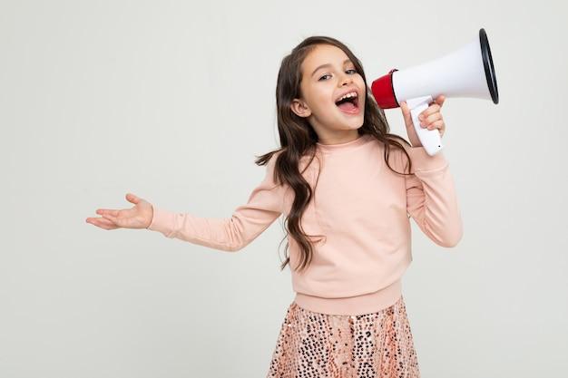 Europäisches lächelndes mädchen mit einem megaphon spricht eine rede auf einer weißen studiowand mit leerzeichen
