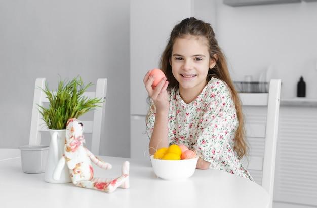 Europäisches mädchen 10 jahre alt in der küche am tisch mit rosa und gelben ostereiern und einem spielzeugkaninchen