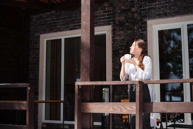Europäisches mädchen, das auf der terrasse ihres häuschens steht und tee oder kaffee trinkt. junge hübsche frau mit braunem haar, die sonnenlicht genießt. person trägt freizeitkleidung. modernes backsteinhaus. sonniger tag