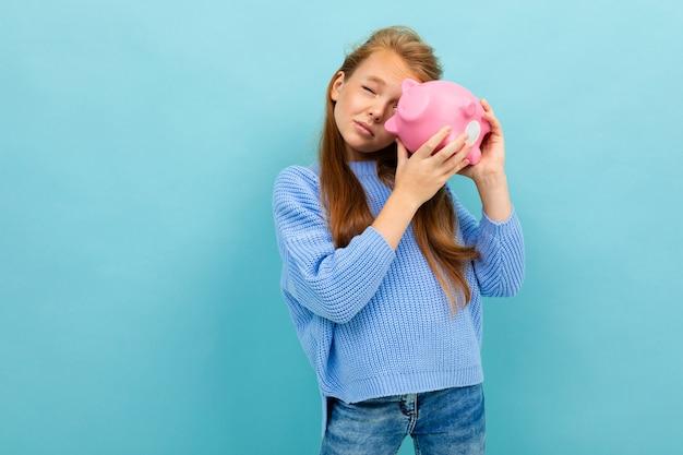 Europäisches mädchen, das ein sparschwein in ihren händen auf hellblau hält
