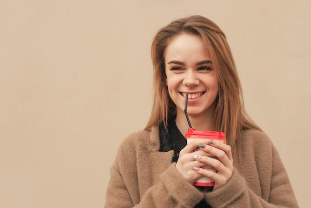 Europäisches mädchen, das eine tasse kaffee in ihren händen hält, einen mantel trägt, der seitwärts schaut und gegen den hintergrund einer beigen wand lächelt