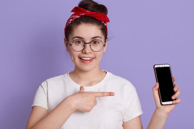 Europäisches mädchen, das leeren handybildschirm mit vorderfinger und mit charmantem lächeln zeigt, frau mit weißem lässigem t-shirt und rotem haarband