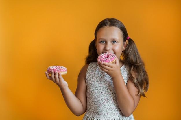 Europäisches mädchen, das zwei donuts hält
