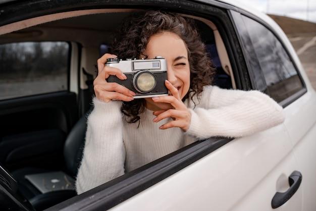 Europäisches mädchen fotografiert auf alter kamera vom persönlichen auto. junge schöne lockige frau ist konzentriert und lächelt