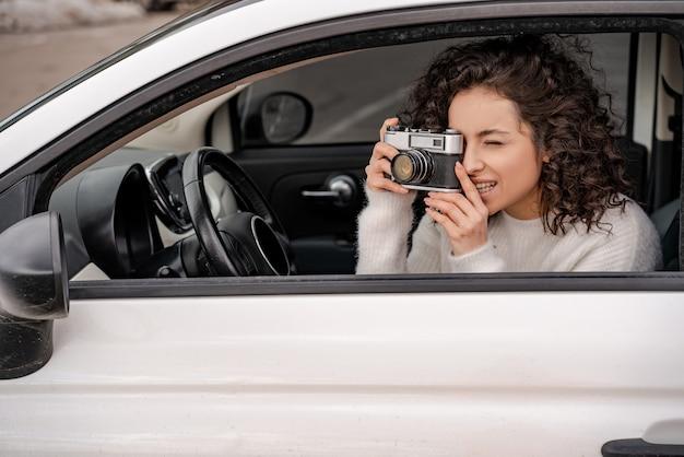 Europäisches mädchen fotografiert auf alter kamera vom persönlichen auto. konzentrierte junge schöne lockige frau