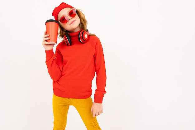 Europäisches mädchen mit kopfhörern und sonnenbrille und einem glas kaffee in der hand