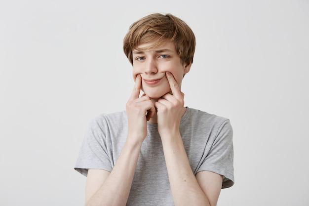 Europäisches männliches model sieht aus, hält die finger auf den wangen, versucht sich zum lächeln zu bringen, isoliert vor grauem hintergrund. trauriger blonder junger mann, der lässig gekleidet ist, macht drinnen gesichter