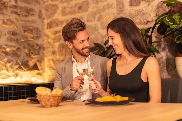 Europäisches paar, das in einem schönen restaurant zu abend isst und valentinstag feiert