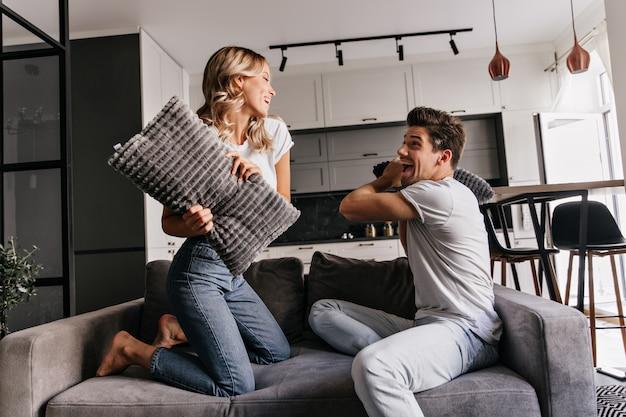 Europäisches paar, das während der kissenschlacht aufwirft. innenporträt der lachenden jungen leute, die im wohnzimmer chillen.