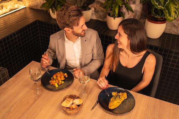 Europäisches paar in einem restaurant, das spaß daran hat, zusammen mit essen zu abend zu essen, valentinstag zu feiern, von oben geschossen