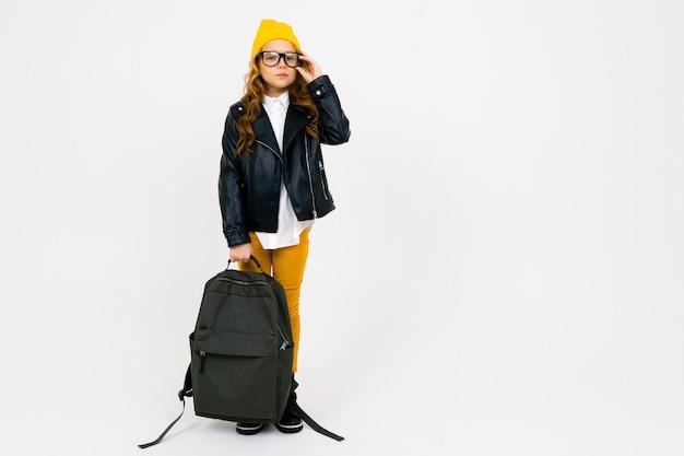 Europäisches schönes schulmädchen, gekleidet in einen gelben hut, eine brille und eine lederjacke mit einem rucksack in der hand in vollem wachstum auf weiß