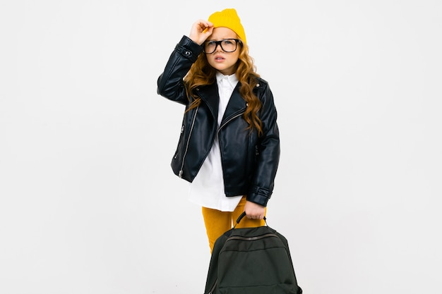 Europäisches schönes schulmädchen gekleidet in einen gelben hut, eine brille und eine lederjacke mit einem rucksack in der hand in voller wachstum auf weißer wand mit copyspace