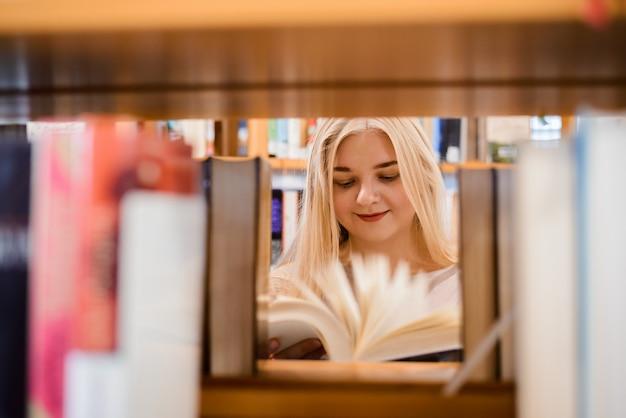 Europäisches studentenmädchen, das durch verschiedene bücher schaut
