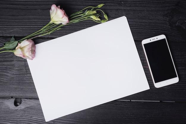 Eustomablume mit leerem weißbuch und handy auf hölzernem schreibtisch