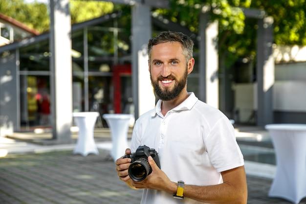 Event hochzeitsfotograf mit kamera in händen, bart und lächeln