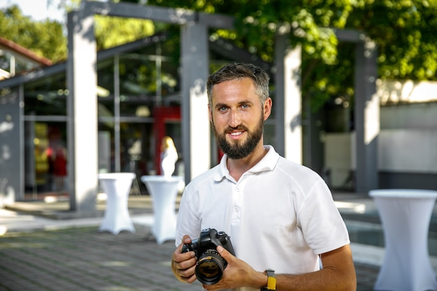 Event hochzeitsfotograf mit kamera in händen, bart und lächeln Premium Fotos