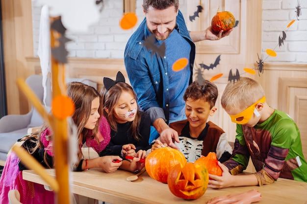 Event manager. bärtiger hübscher eventmanager, der kindern hilft, halloween-kostüme zu tragen, die kürbisse verzieren