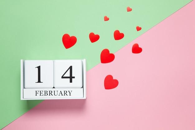 Ewiger kalender mit datum vom 14. februar, rote konfettiherzen unterschiedlicher größe auf zweifarbigem hintergrund in rosa und grün. flach liegen. draufsicht.