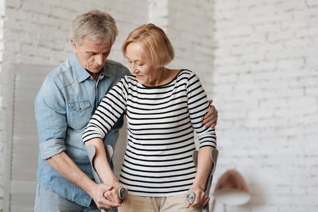 Ewiges vertrauen. bemerkenswerte geduldige starke dame, die sich von einer verletzung erholt und die krücken benutzt, um sich zu bewegen, während ihr mann ihr hilft