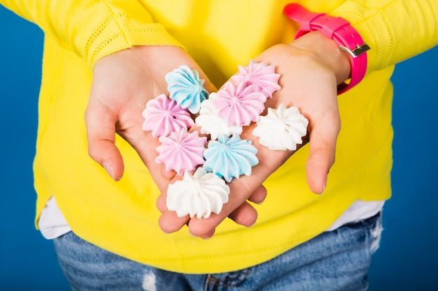Ewoman in der gelben bluse auf blauem halten in den handbaisern, die süßes essen genießen