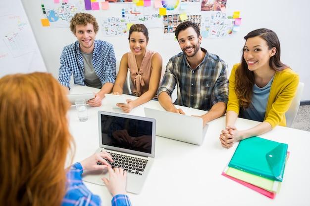 Executive diskutiert über laptop mit ihren kollegen während des meetings