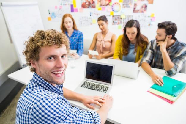 Executive diskutiert über laptop mit seinen kollegen während des meetings