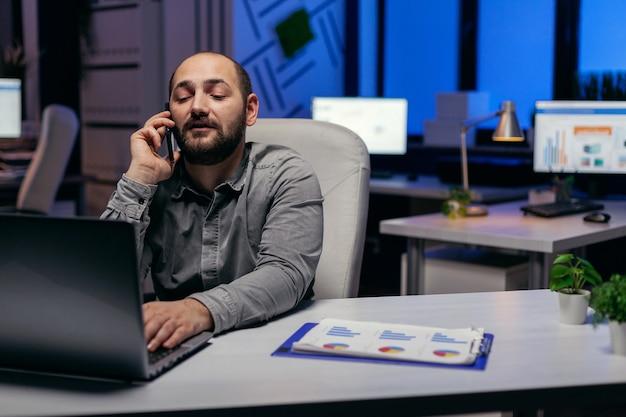 Executive geschäftsmann mit handy sprechen über frist. manager, der ein geschäftsgespräch mit smartphone führt, während er überstunden im büro macht.