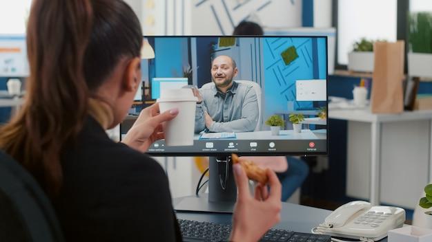 Executive manager isst pizza zum mitnehmen während einer online-videokonferenz-konferenz