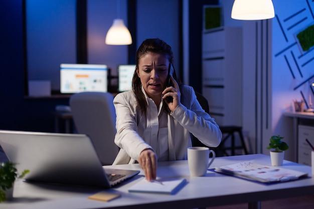 Executive managerin spricht am telefon, während sie spät in der nacht finanznotizen überprüft