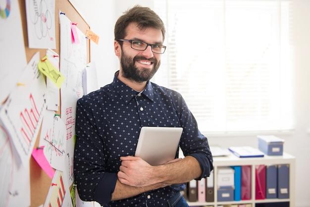 Executive posiert im büro mit einem digitalen tablet