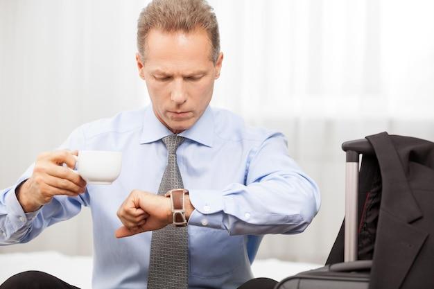 Exekutive in eile. selbstbewusster mann mit grauen haaren im hemd, der die zeit überprüft, während er auf dem bett sitzt
