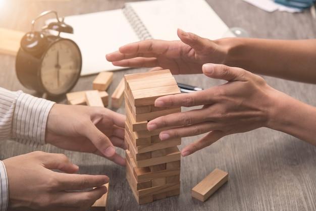 Exekutivkooperation, die holzblock auf das turmspiel setzt