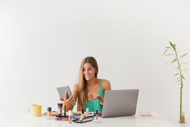 Exemplarplatzfrau am schreibtisch mit schönheitsprodukten