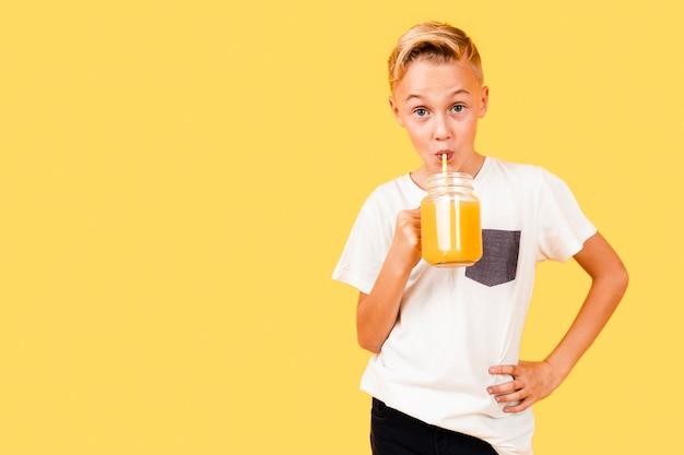 Exemplarplatzjunge, der die orange frisch trinkt