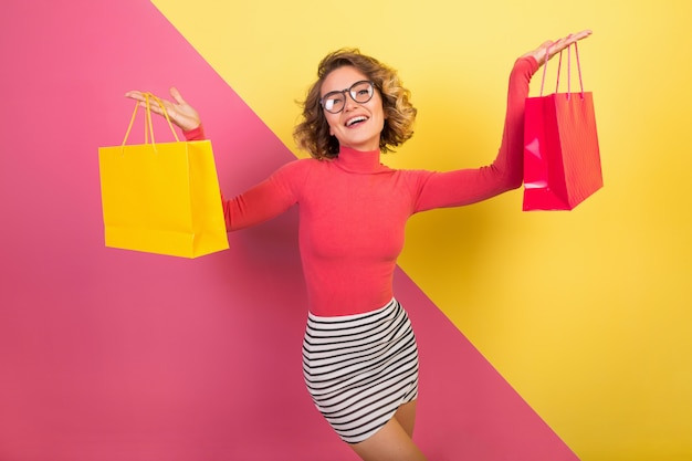 Exited attraktive frau im stilvollen bunten outfit, das einkaufstaschen hält