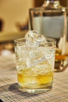 Exklusiver whisky im glas mit eis auf dem hintergrund der flasche