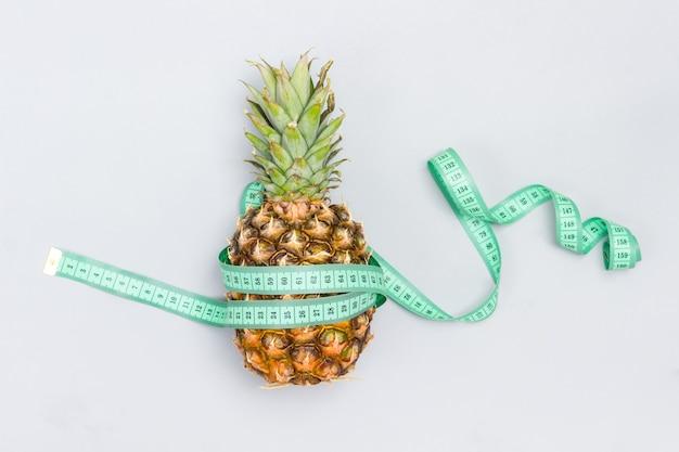 Exotische ananas ist in maßband eingewickelt. grauer hintergrund. flach legen