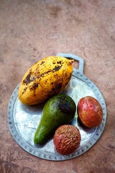 Exotische früchte auf einem teller auf betonhintergrund