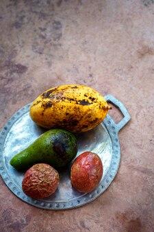Exotische früchte auf einem teller auf einem betontisch