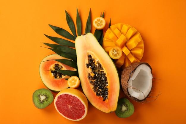 Exotische früchte auf orangem hintergrund, ansicht von oben.